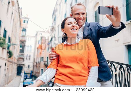 Happy smiling couple take a selfie photo on the old Venice street
