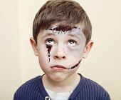 little cute boy with facepaint like zombie apocalypse at halloween party close up on white background poster