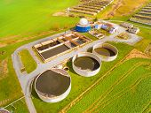 Aerial view to biogas plant from pig farm in green fields. Renewable energy from biomass. Modern agriculture in Czech Republic and European Union.  poster