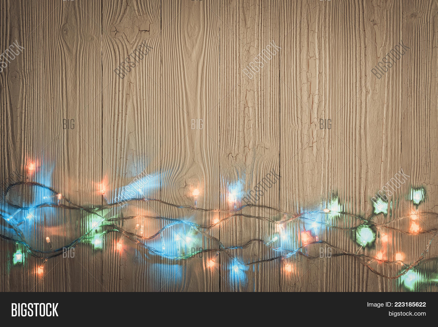 Fancy blinker light bulbs or garlands and wreath on wood table for Christmas or New years