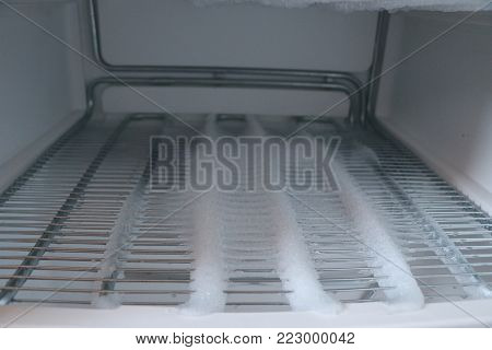 Freezer Compartment With An Open Door. The Freezer Covered With Snow And Ice Is Open For Defrosting.