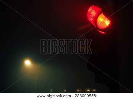 Closeup view of semaphore, red light and foggy night atmosphere.