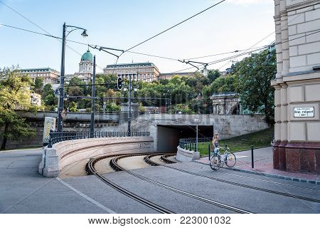 Budapest, Hungary - August 14, 2017: Scenic view of woman with bicycle crossing the tramway tracks against Buda castle