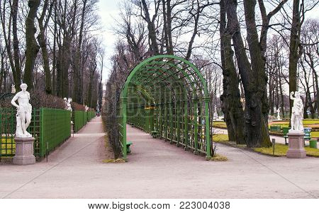 Arch arches and statues of the main avenue in the Summer Garden park in early spring in April before the opening of the summer park in St. Petersburg