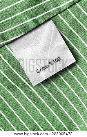 Fabric composition clothes label on green striped cotton background