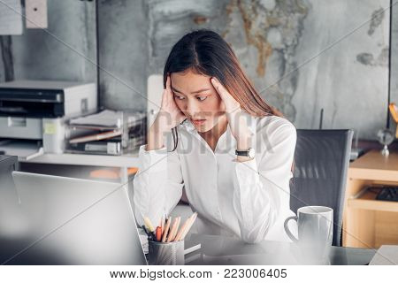 Frustrated Asian businesswoman cover her face with two hand and feel upset from work in front of laptop computer on desk at office,Stress office lifestyle concept