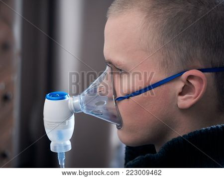 The man inhales the medication through the nebulizer. Portrait