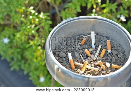 Stainless ashtray and cigarette stubs at the smoking area in gas station with green blurred green bush background.Concept is smoke in the area provided,World No Tobacco Day.