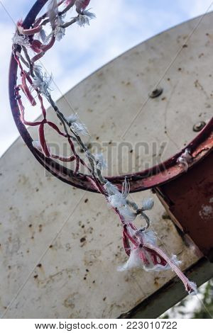 old broken basketball hoop on a rusted white backboard