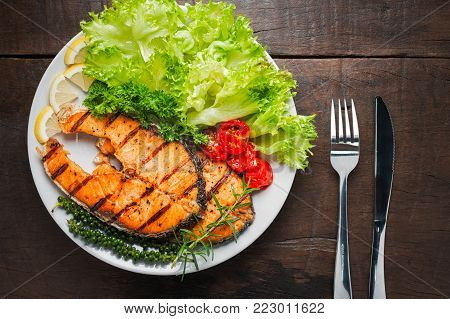 Grilled salmon steak served with grilled tomatoes, salad, lemon sliced, pepper seeds, rosemary, parsley on white plate on wooden table.