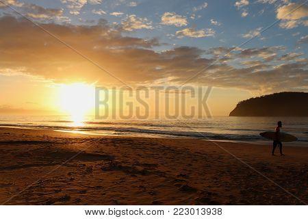 surfer on empty beach during sunrise, orange sunrise over sandy beach, pristine coastline during dawn. coastline with island in distance.