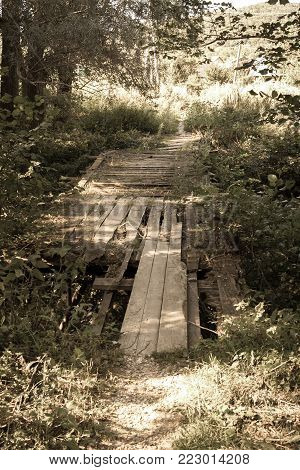 Old dilapidated bridge over overgrown creek. Toned image.