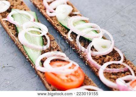 Long crusty baguette. warm, freshly rye baked bread with cheese, cucumber and tomatoes with onions on a rustic background. Cut the slices. healthy eating concept. French pastries. top view.