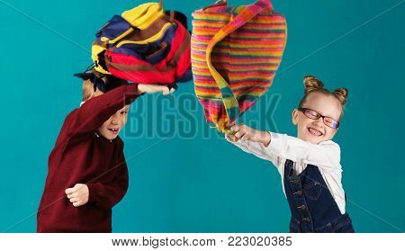Funny little kids with big backpack jumping and having fun against turquoise wall. School concept. Back to School. School's out for summer. Celebrating the end of another successful school year. children fight backpacks