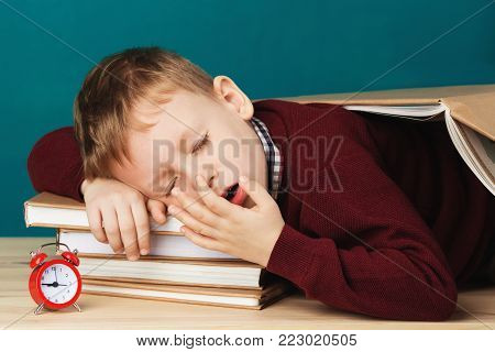 tired school boy asleep on books. little student sleeping on textbooks. Child in school uniform lies on the table with big pile of books against blue wall. Eyes closed. School concept. Back to school