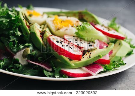 Homemade Fresh spring salad with rucola, radish with red onion and avocado with eggs in white bowl on chalkboard background. healthy winter vegetarian food