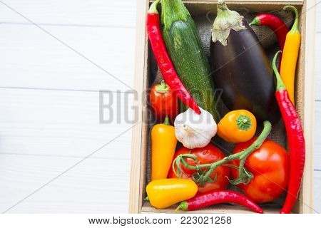 Preparing Healthy Food, Vegeterian, Vegan Concept. A box of fresh whole vegetables: zuccini, eggplant, tomatoes, chilli peppers and garlic, white wooden background, top view