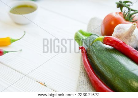 Preparing Healthy Food, Vegeterian, Vegan Concept. A set of fresh whole vegetables: zuccini, tomatoes, chilli peppers and garlic on a wooden table, top view, mcopy space