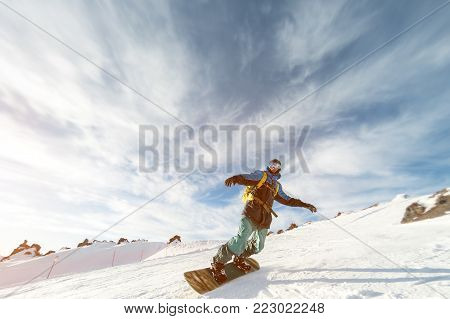 A snowboarder in a ski mask and a backpack is riding on a snow-covered slope leaving behind a powder of snow against the blue sky and the setting sun. Photo in motion