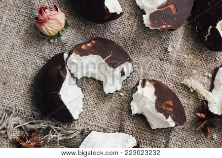 marshmallows in chocolate glaze, part of one bitten off on background of fabric from flax. Broken cakes. Decorated with dry flowers of roses. top view