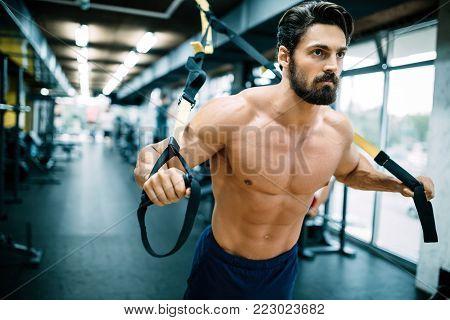 One caucasian man exercising suspension training trx