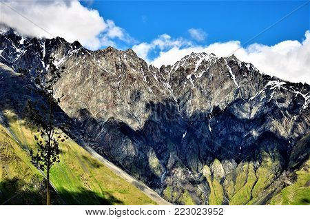 a large landform that stretches above the surrounding land in a limited area, usually in the form of a peak.