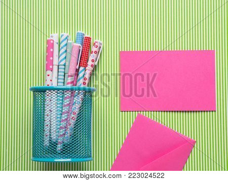 Colorful girlish pens on green striped background. Flat lay with pink card and envelope