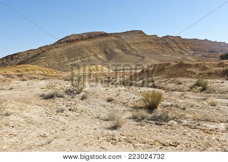 Rocky hills of the Negev Desert in Israel. Breathtaking landscape of the desert rock formations in the Southern Israel Desert. Dusty mountains interrupted by wadis  and deep craters.