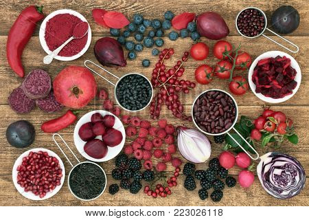 Health food with fruit, vegetables, grain and pulses high in anthocyanins, antioxidants, minerals and vitamins on rustic oak background. Healthy eating concept. Top view.