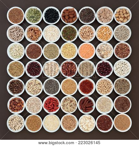Large dried high fiber health food selection in white porcelain bowls with foods high in omega 3 fatty acids, antioxidants, anthocynins and vitamins. Top view.