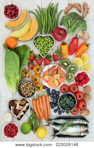 Healthy food nutrition concept with fresh seafood, fruit, vegetables, nuts, herbs and spice. Super foods high in omega 3, antioxidants, anthocyanins, fibre, minerals and vitamins. Top view.