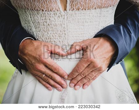 Groom creating heart shape with his hands on the back of the bride.Couple in love. Close up of hands. Young couple has done heart shape hands in their wedding day. Bride and groom, embrace.