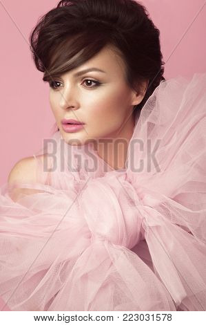 Fashion beautiful woman in black dress with bow, retro make-up and hair. Beauty face and body. Photo taken in studio on a pink background