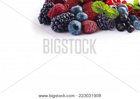 Mix berries isolated on a white. Ripe blueberries, blackberries, red currants, black currant, raspberries and strawberries. Various fresh summer berries on white background. Berries and fruits with copy space for text. Background berries.