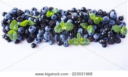 Black and Blue berries isolated on a white. Ripe blueberries, blackberries with mint on white background. Berries with copy space for text. Background berries. Top view.