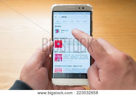 Zhongshan,China-January 13, 2018:Chinese man getting an Alipay red pocket on the mobile.Alibaba sends out lots of free red pockets as gift to users in 2017 & 2018.