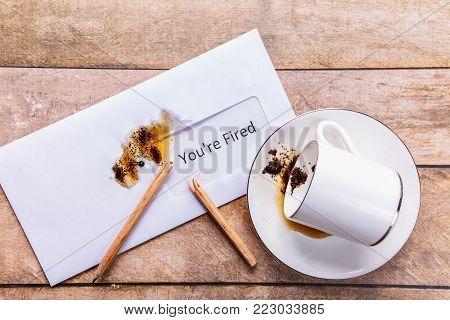 You are fired the letter and coffee spilled on a desk. Concept of jobless and depressed. The broken pencil as a failure symbol.