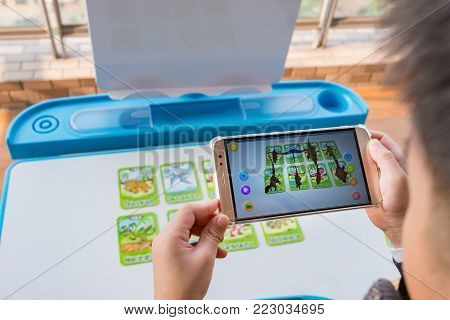 Zhongshan,China-December 30, 2017:kid playing Augmented Reality popup of the dinosaurs via mobile. AR and VR games become more and more popular.