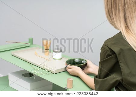 Nice girl holds an emerald bowl on the green metallic-wooden stand on the gray wall background in a studio.  On the stand there is white box, colorful metal supports, jar, tea whisk, flower's branch.