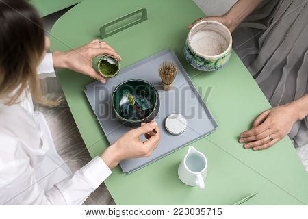 Girls preparing a chinese matcha green tea on the green metal table indoors. One woman measures tea powder with a wooden stick over the bowl. On the table there is tea whisk and white jug with water.