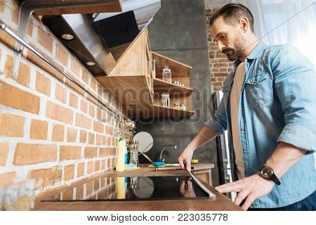 Cooker length. Attractive pleasant bearded man posing in profile while staring down and measuring surface