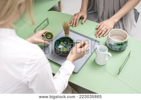 Cute girls preparing a chinese matcha green tea on the green metal table indoors. One woman puts tea powder into the colorful bowl. On the table there is a wooden tea whisk and white jug with water.