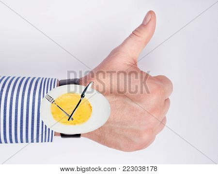 Concept of healthy protein nutrition, protein diet. Hand with a clock egg as a symbol of day meals. knife, fork as arrows