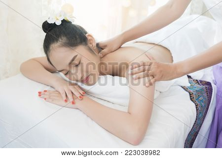 Beautiful young Asian woman relaxing , lying on massage table and having Thai traditional massage in spa salon