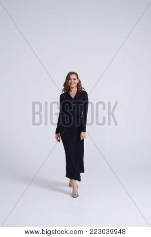 Full-length shot of smiling girl in stylish black dress walking towards camera