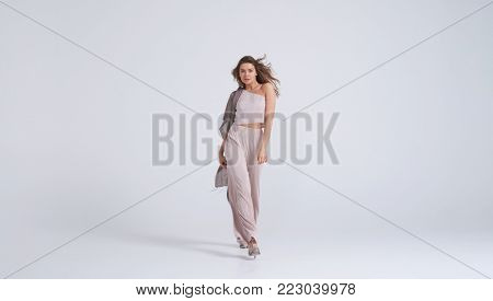 Full-length shot of fabulous young woman in stylish outfit walking towards camera
