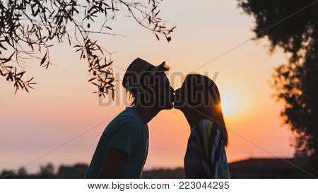 Young couple kissing in sunset by the seaside