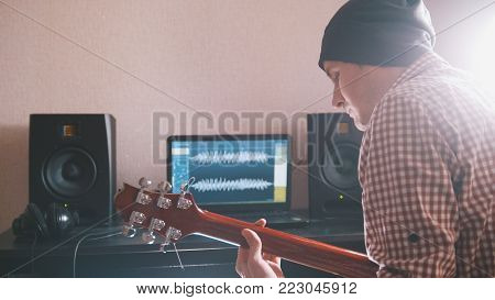 Young man in hat musician composes and records soundtrack playing the guitar using computer, headphones and keyboard, focus on equipment