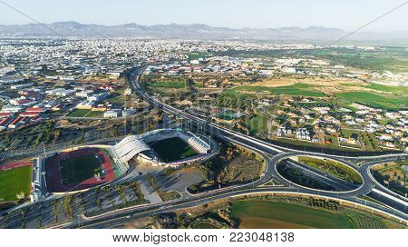 Nicosia, Cyprus - 25/12/2017: Aerial bird's eye view of GSP football stadium, highway A1 and round about at Latsia. The city, soccer field, athlete track, seats and auxiliary pitch from above.