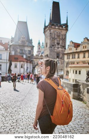 a young smiling woman tourist in sportswear and small orange backpack in the center of Prague. travel guide, tourism in Europe, woman tourist on the street